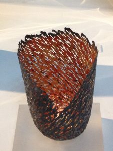 An image of a vessel formed from a discarded food can, with applied copper leaf and 23 carat red gold.