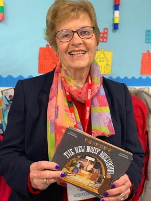 Joan Wyn Jones holding a copy of the Noisy Neighbour nativity story book.